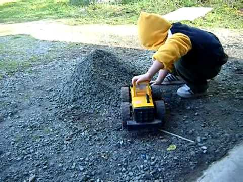 Kid Plays With Toy Digger And Big Pile Of Rocks