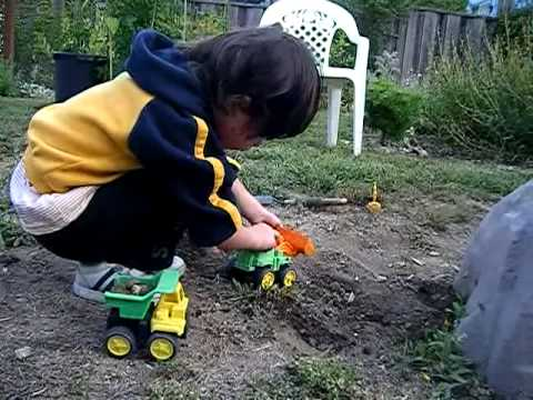 Kid Plays With Toy Diggers in Dirt At Grandmas