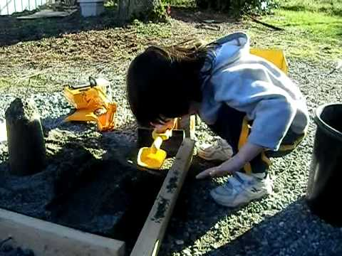 Kid Plays with Diggers In New Sand Pit