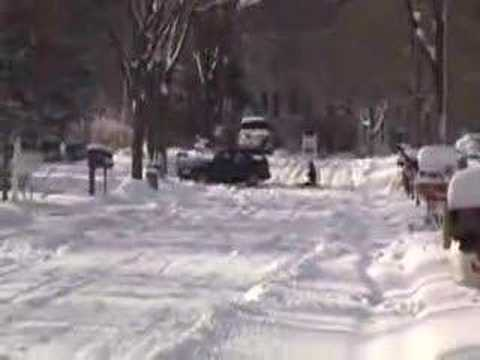 Snow sledding behind a car