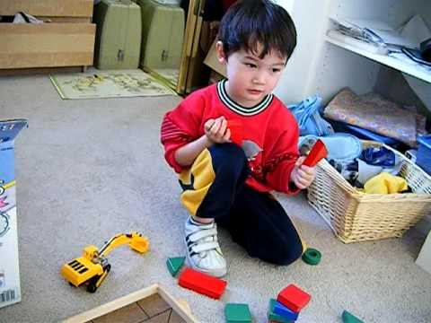 Kid Builds House With Red Triangle Toy Blocks