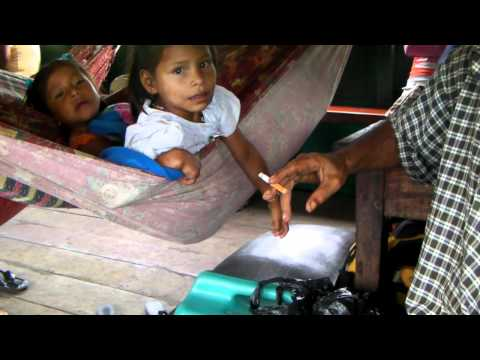 Crazy guy smoking over a gas can next to a little girl on an Amazon boat