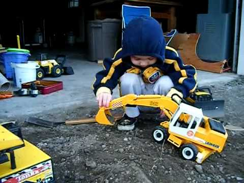 Kid Plays With Toy Diggers & Trucks, Then Rides A Trike, Says Hi!